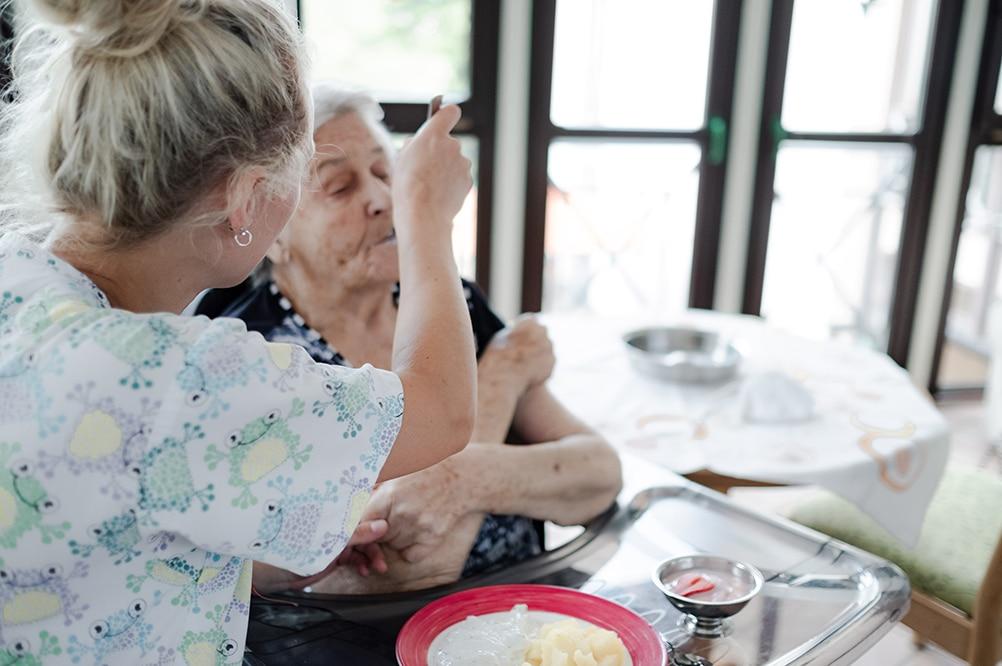 Pflegerin hilft Bewohnerin beim Essen