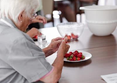 Seniorin schneidet Erdbeeren