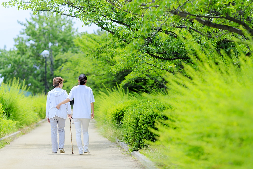 Pflegerin und Seniorin gehen spazieren